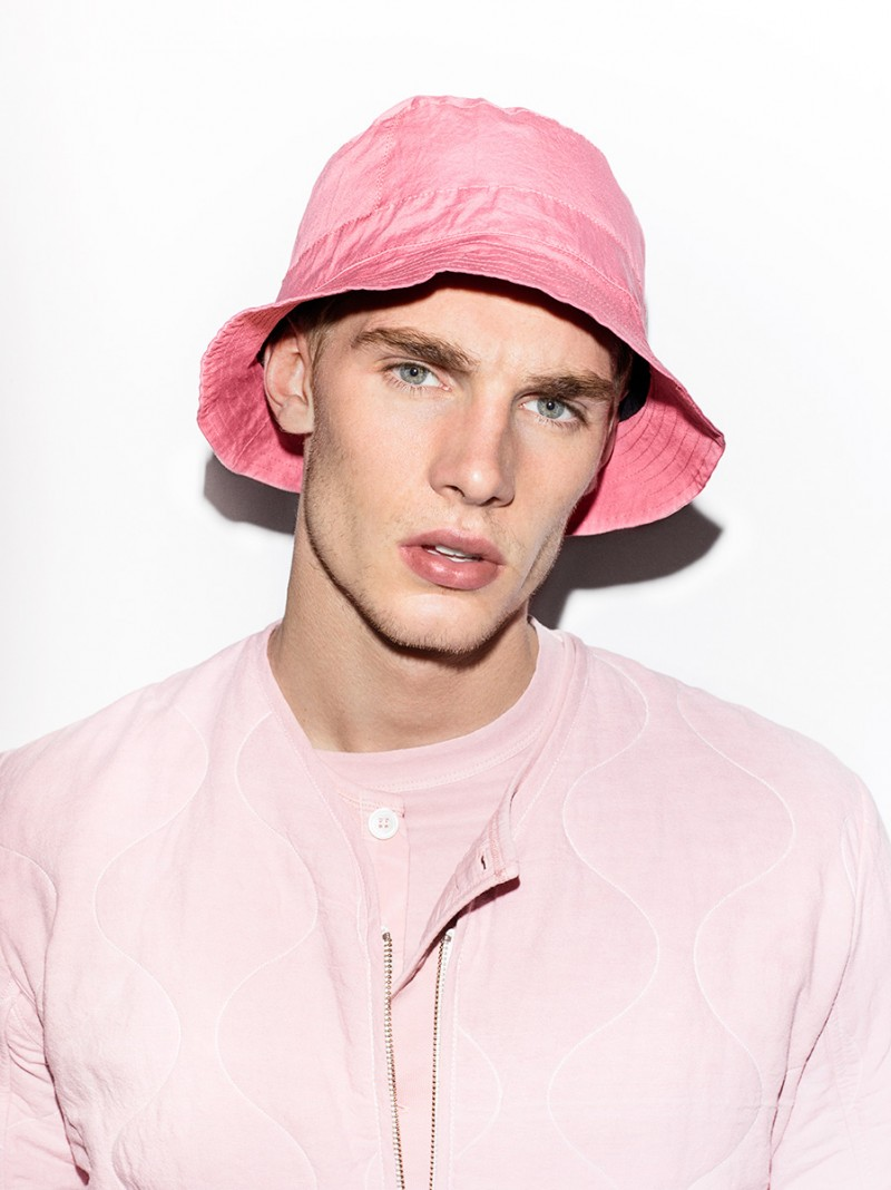 Tommy Marr is handsome in pink, wearing a spring Our Legacy look, topped off with a bucket hat.