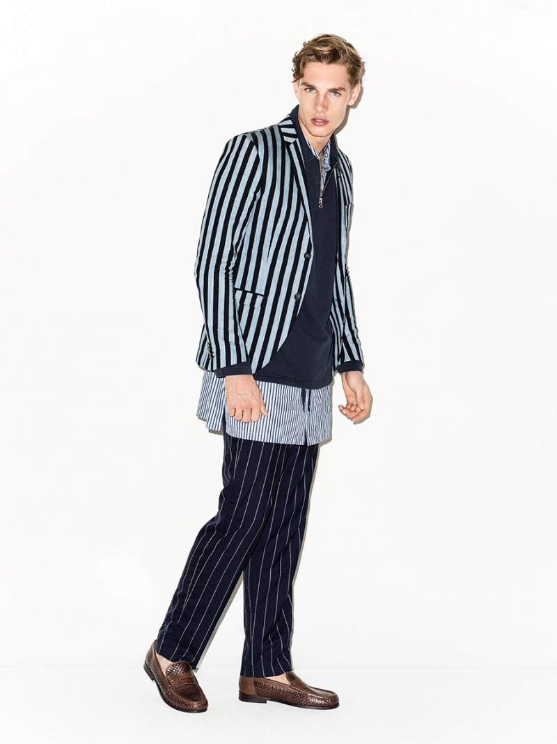Playing with stripes, Tommy Marr is photographed in a Tiger of Sweden blazer with GANT Rugger trousers and an enlongated shirt from Acne Studios.