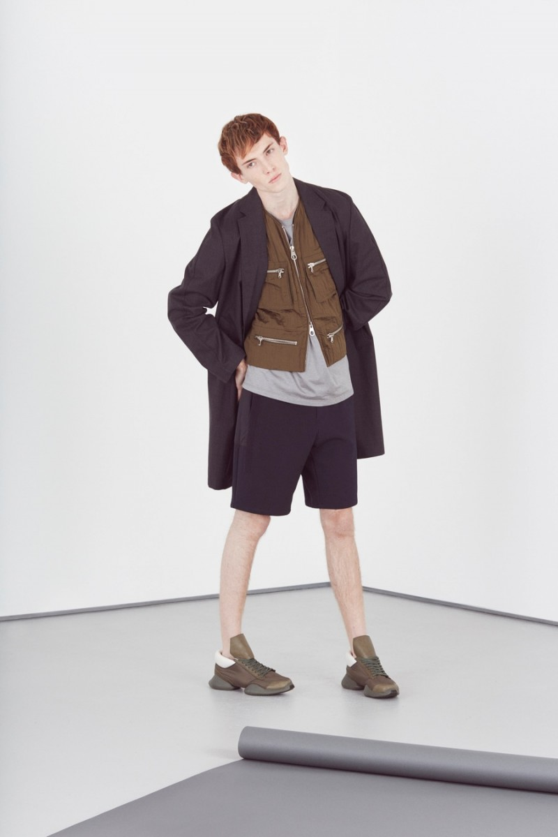 Theo George wears metallic t-shirt Paul Smith, relaxed shorts OAMC, running sneakers Adidas x Rick Owens, single-breasted overcoat and zipped vest Wooyoungmi.