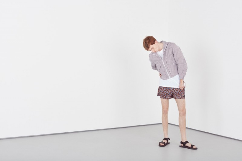 Theo George wears striped short jacket CMMN SWDN, relaxed t-shirt Jil Sander, printed swim shorts Acne Studios and leather sandals A.P.C.
