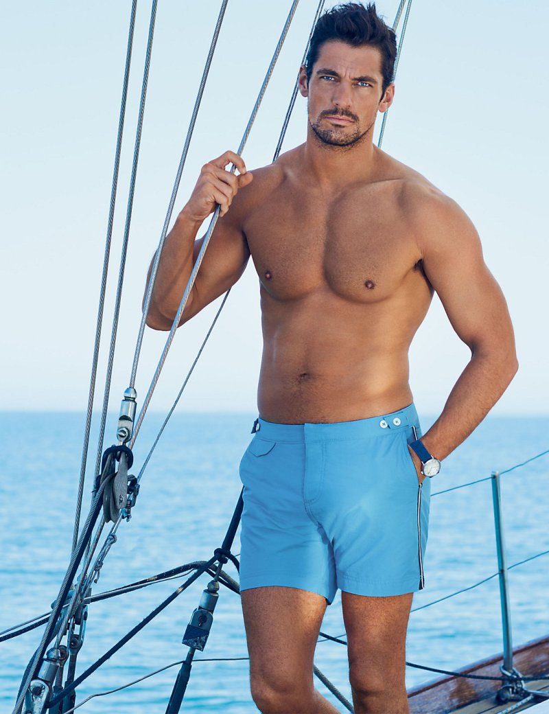 David Gandy appears in a new outing for Marks & Spencer wearing his David Gandy for Autograph Tailored Fit Mid Length Quick Dry Swim Shorts in blue.