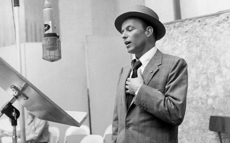 Frank Sinatra captured at a 1950s recording studio in one of his trademark hats.
