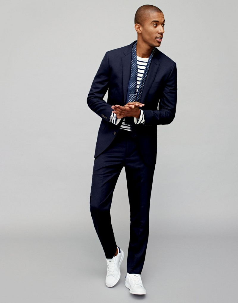 Model Claudio Monteiro sports a trim, tailored J.Crew suit with white Adidas Stan Smith sneakers.