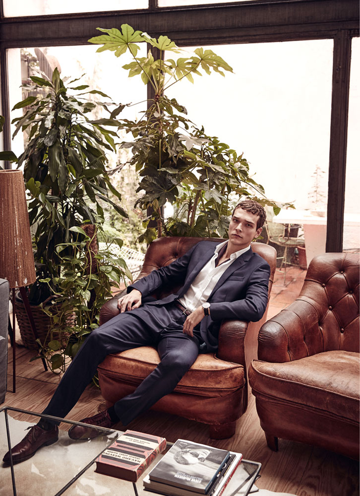 Alexandre Cunha lounges in a navy suit from Hackett.