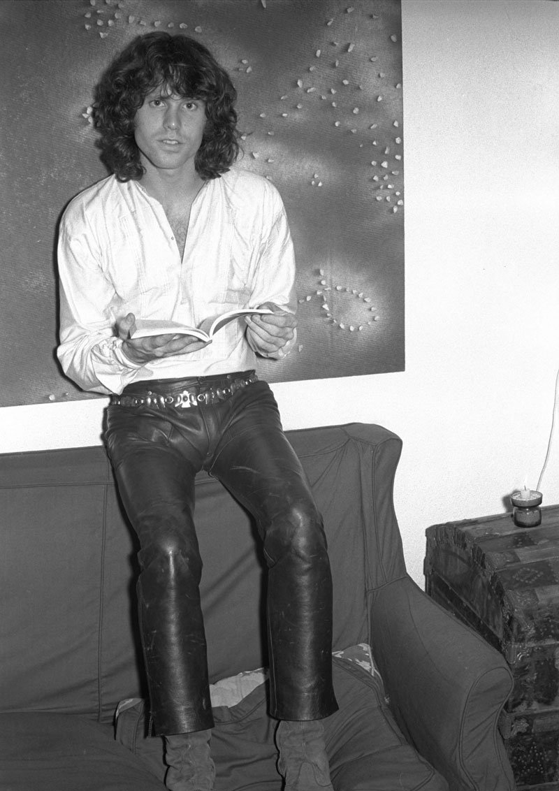 Jim Morrison relaxes in a Bohemian style white shirt with leather pants.