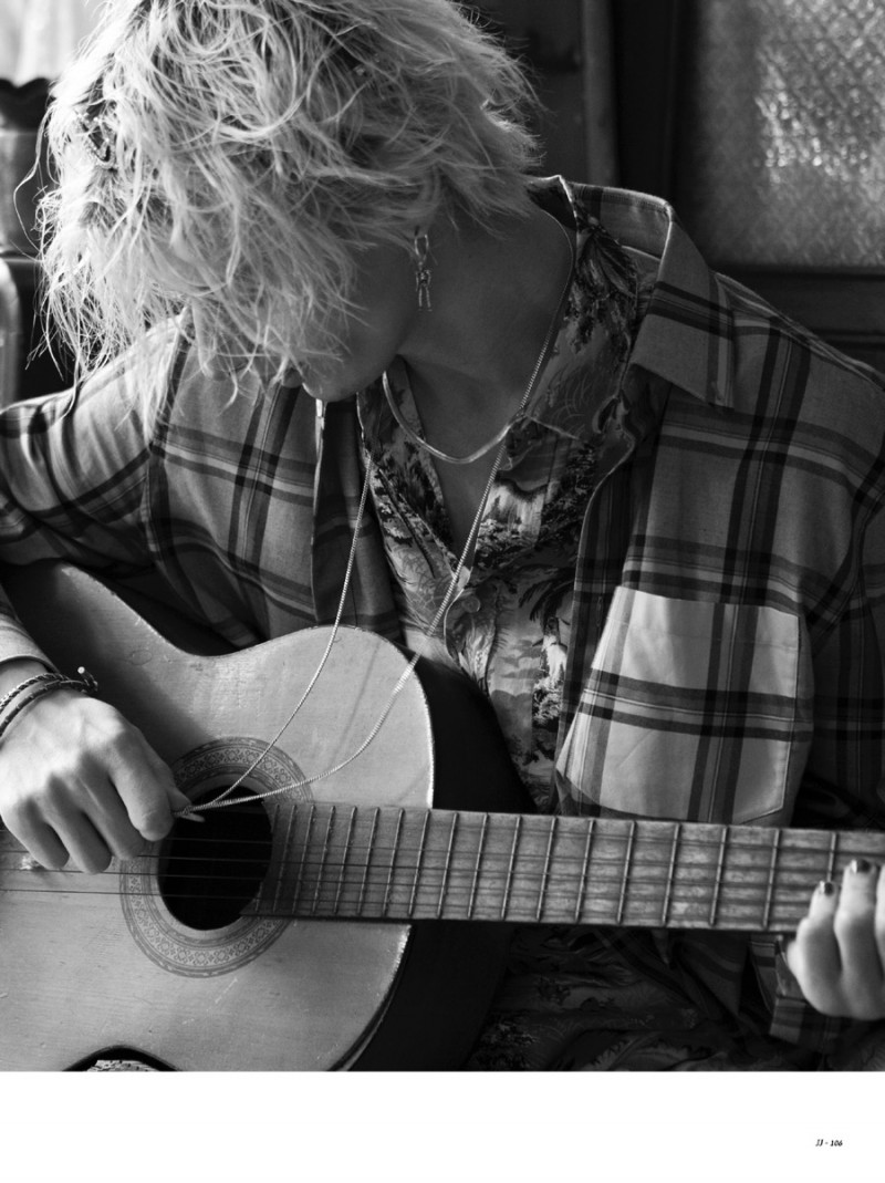 Ivan Claudiu Vlad sports a flannel shirt as he plays the guitar.