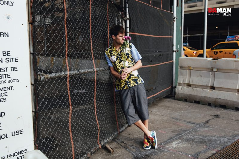 Paolo Anchisi captured in the streets of New York City, wearing a Comme des Garçons floral print short-sleeve shirt and oversized shorts with Christian Louboutin sneakers.