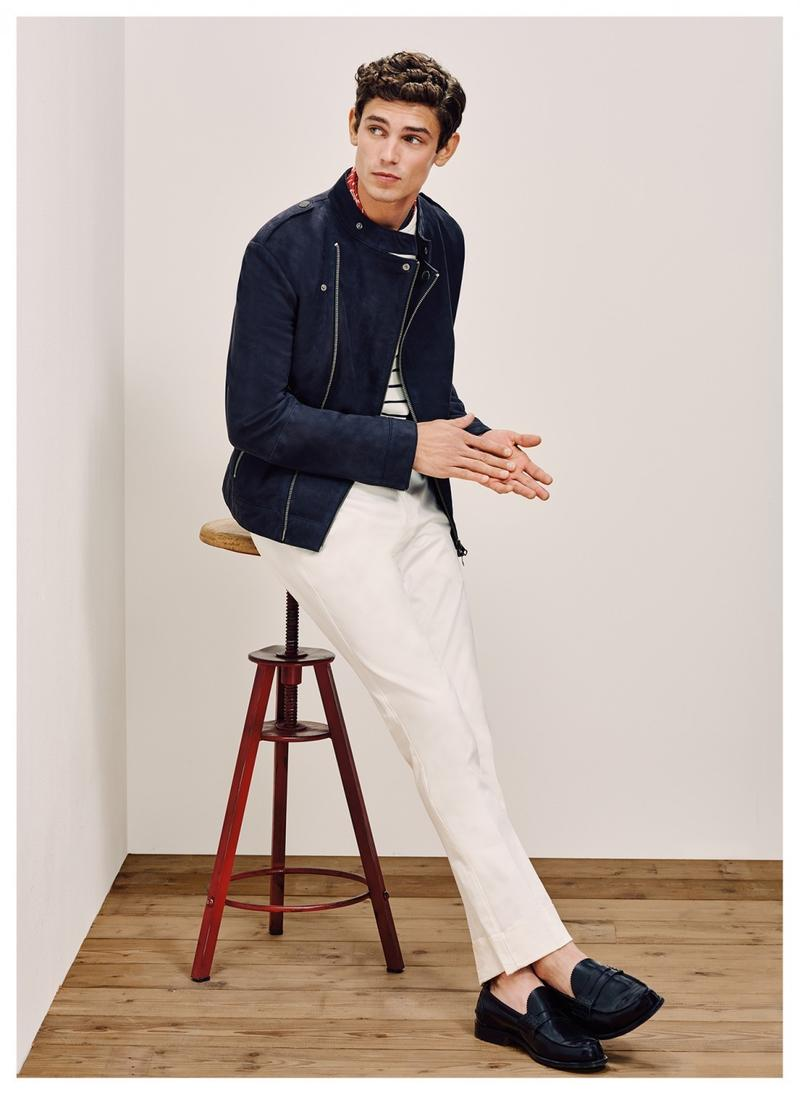 Arthur Gosse is captured in a moto jacket, which adds a cool edge to a pair of white trousers from Tommy Hilfiger Tailored.