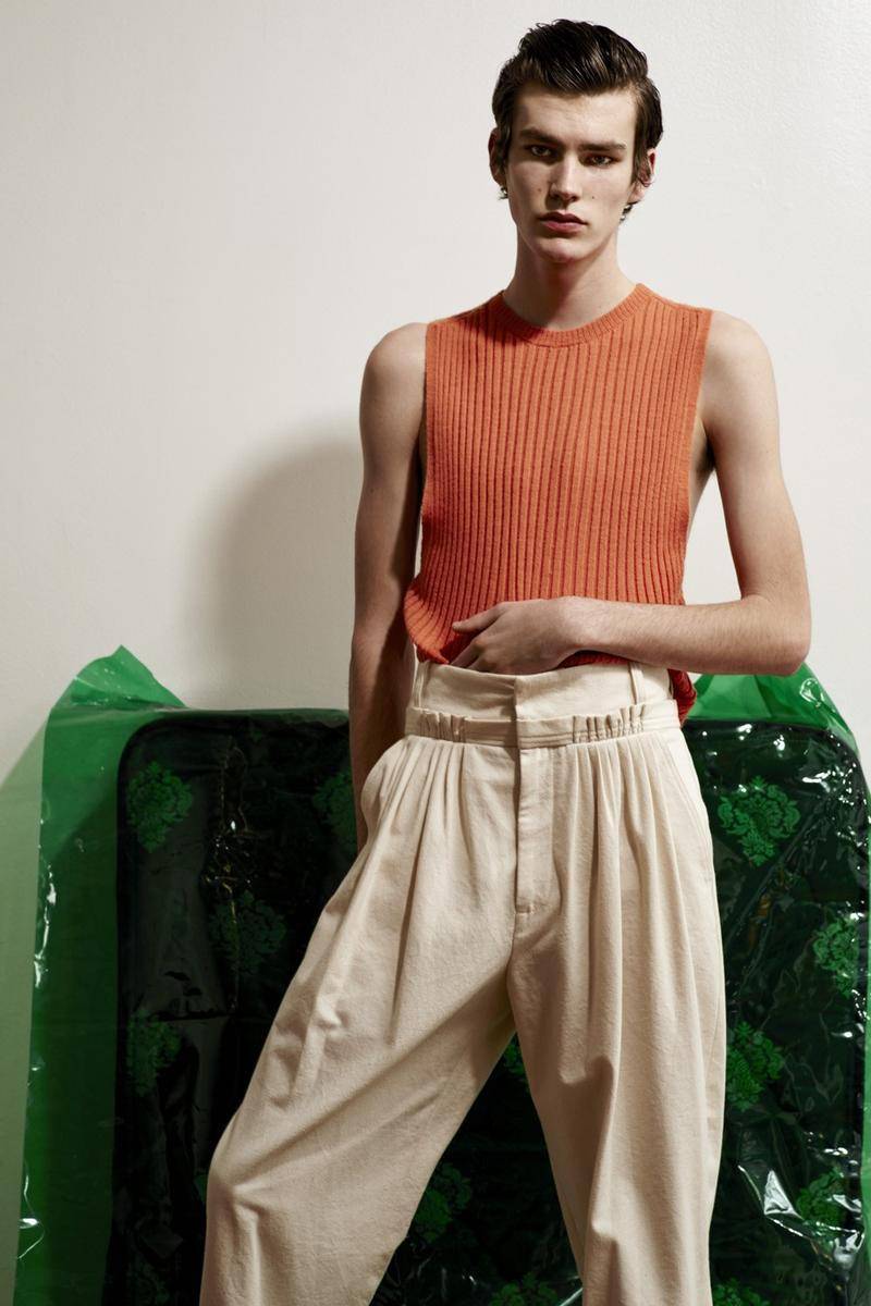 Elias de Poot cuts a lean figure in a sleeveless ribbed top from Acne Studios with a pleated J.W. Anderson trousers.