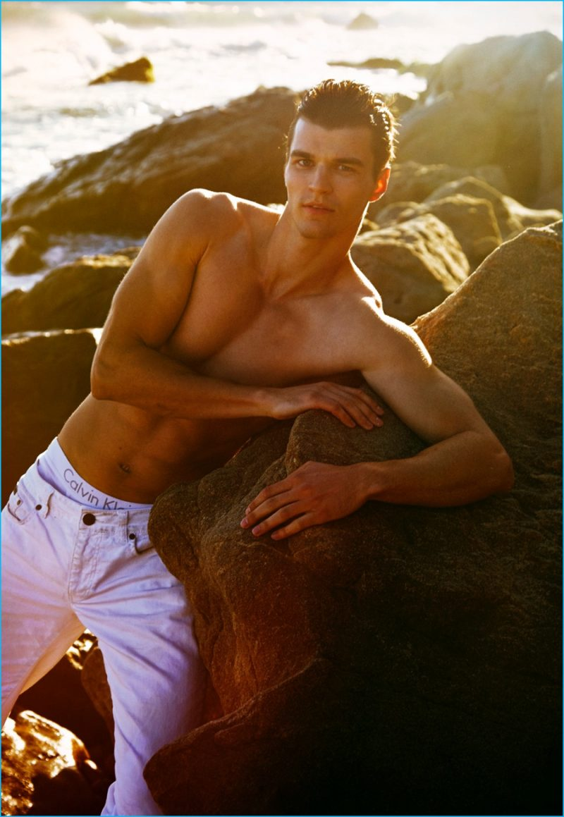 Arran Sly wears white jeans and underwear from Calvin Klein.