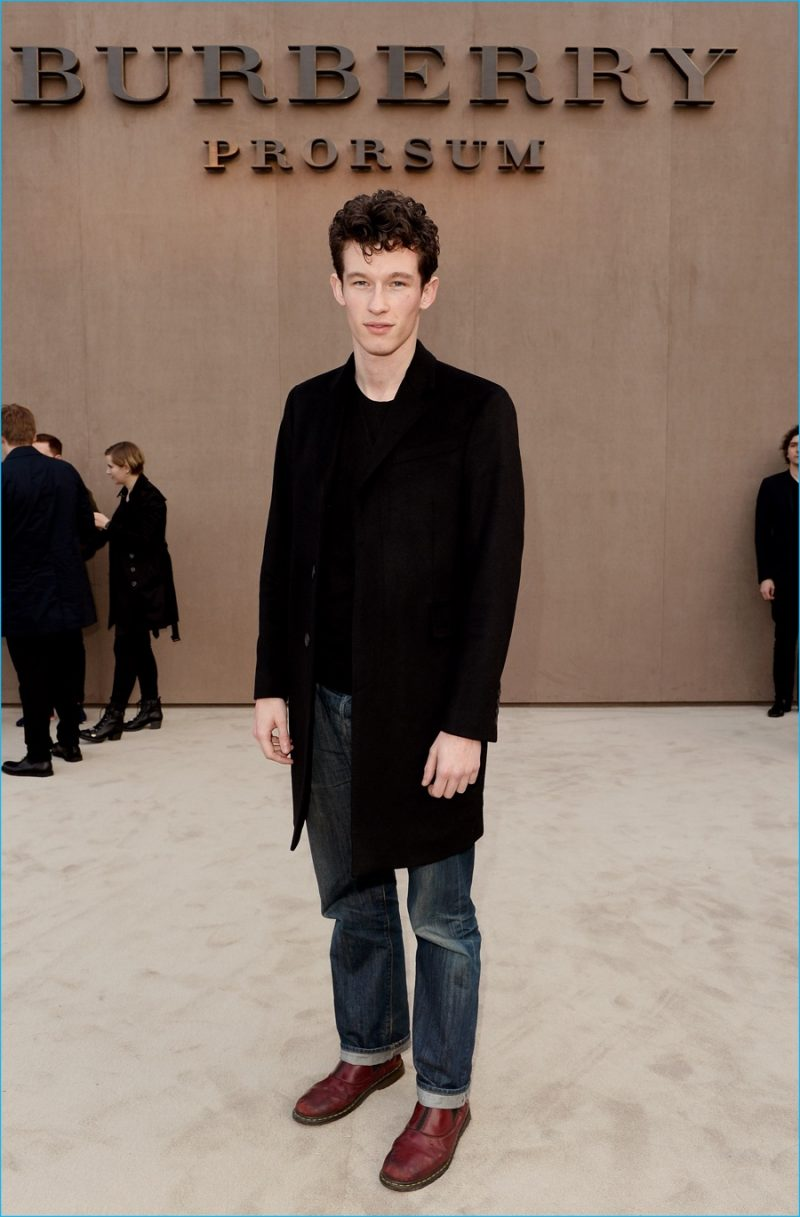Callum Turner poses for pictures at Burberry Prorsum's fall-winter 2014 menswear show.