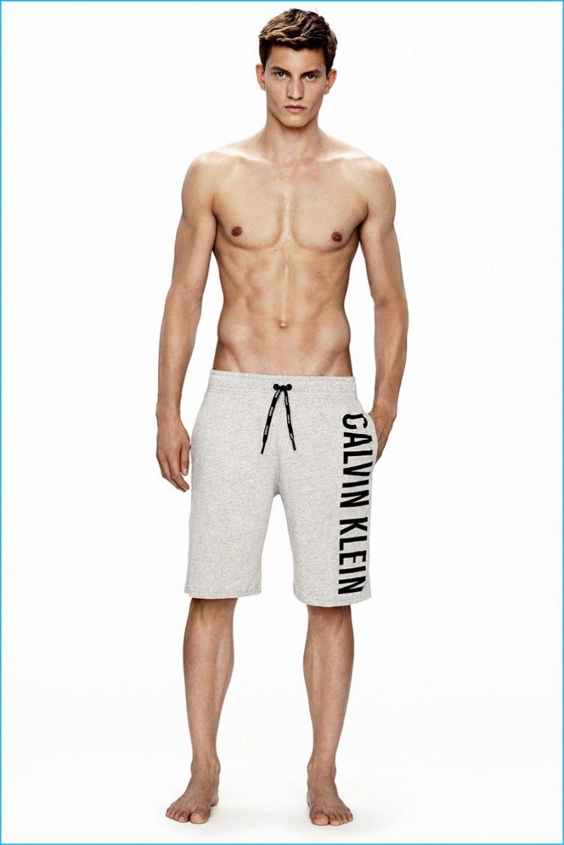 Benjamin Benedek models grey Calvin Klein logo sweatshorts.
