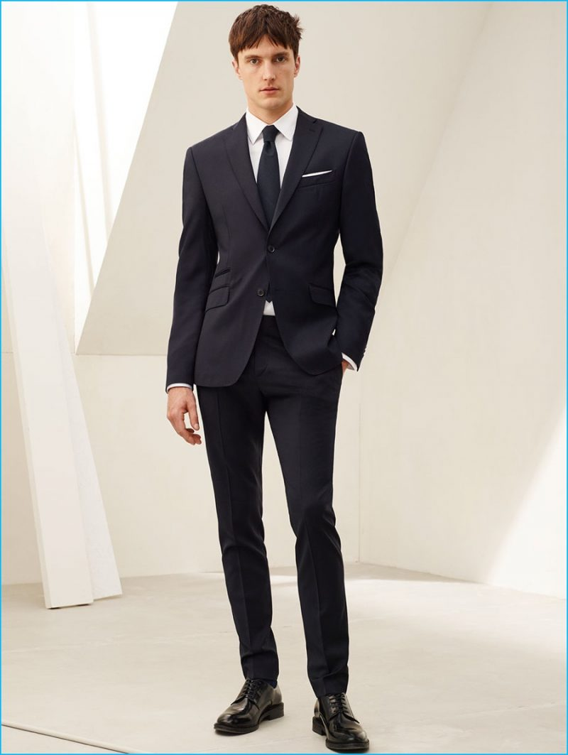 Charlie Timms is a sleek vision in a wool suit, plain stretch shirt, rustic fabric seed tie and antik leather bluchers from Zara Man.