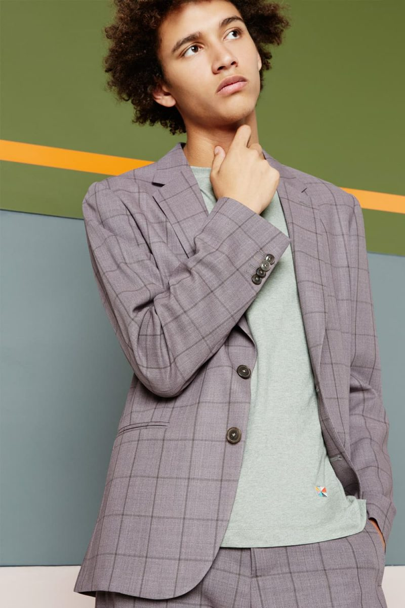 Jackson Hale charms in a windowpane print suit from Paul Smith that has been paired with a sweater.