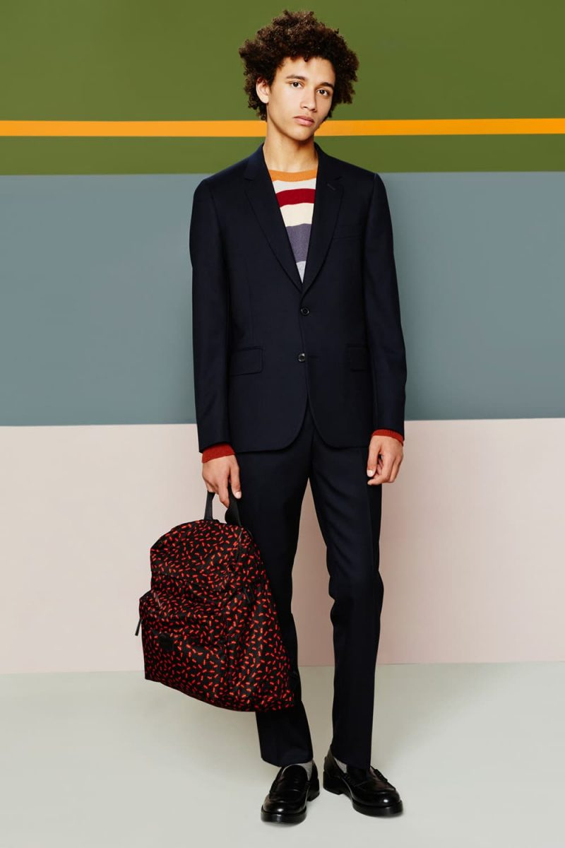 Jackson Hale cleans up in a sleek navy Paul Smith suit, complemented by a striped sweater.