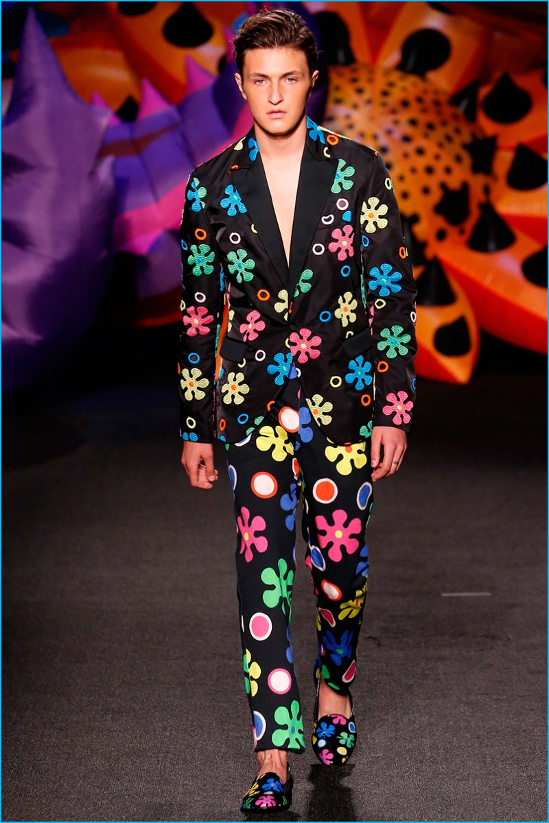 Anwar Hadid makes his runway debut, wearing a groovy flower print suit from Moschino.