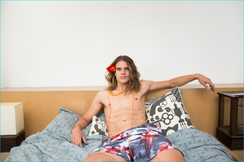 Models William Hawins relaxes in BENCH/Body printed swim shorts.