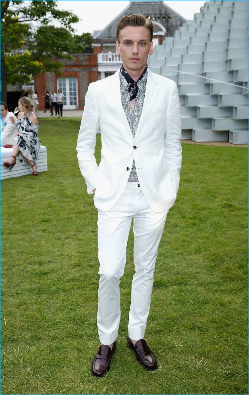 July 2016: Jamie Campbell Bower attends the 2016 Serpentine Summer Party in a white tailored look from Tommy Hilfiger.