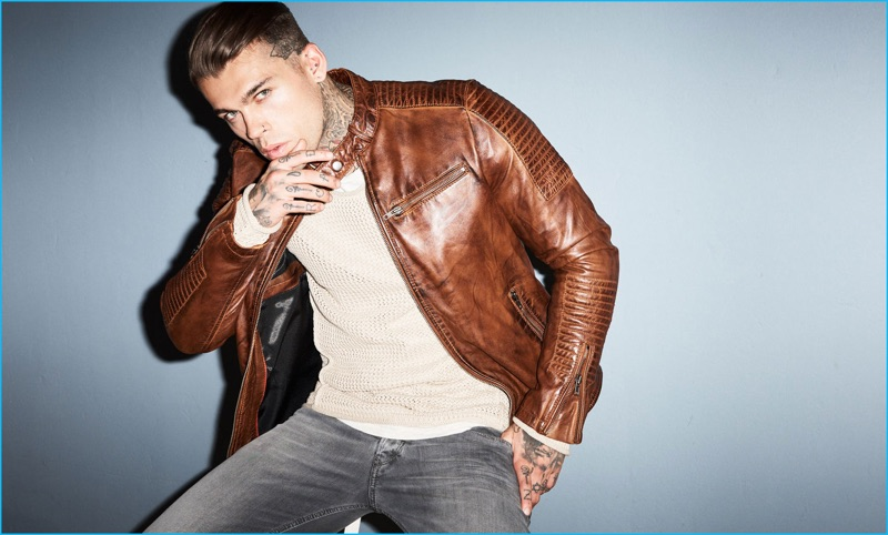 Stephen James sports a pullover and brown leather jacket from Autark with Diesel denim jeans.