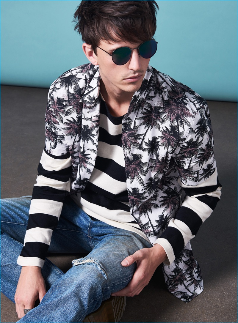Alex Dunstan wears striped sweater Armor Lux, denim jeans Nonnative, loafers Dr Martens, palm print shirt and sunglasses H&M.