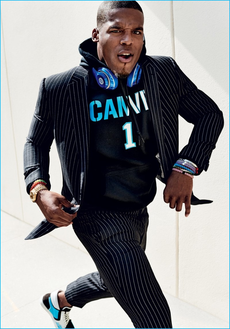 Cam Newton wears a pinstripe Ralph Lauren suit with a King Threads hoodie.