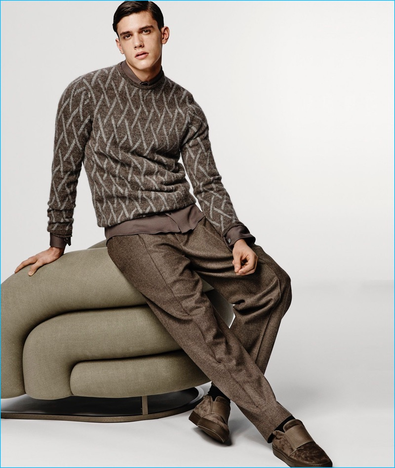 Xavier Serrano warms up to fall browns, wearing a smart sweater and trousers look from Giorgio Armani.