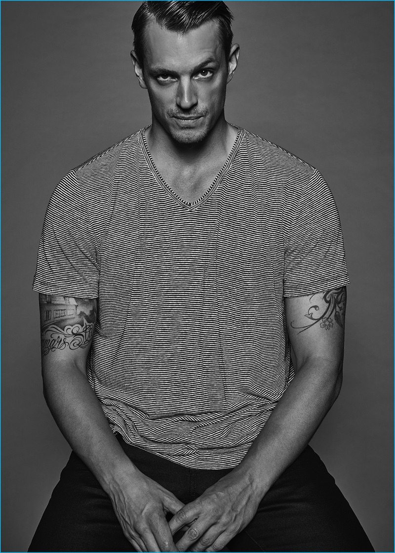 Joel Kinnaman goes casual in a striped AllSaints v-neck and Vince pants.