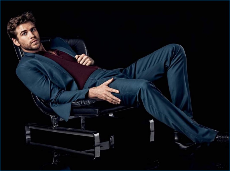 Liam Hemsworth wears a Dolce & Gabbana suit with a H&M polo shirt and Prada dress shoes.