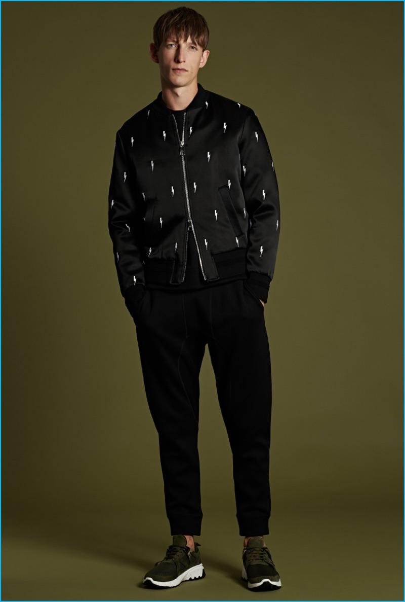 Neil Barrett lightning bolt bomber jacket, black seam-detail sweatpants, kahki suede city sneaker, and white lightning bolt t-shirt.