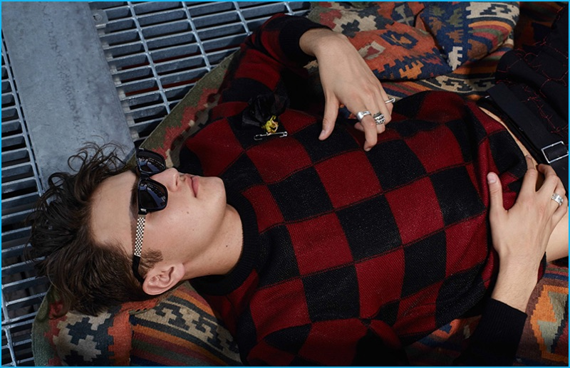 Anwar Hadid plays it cool in a red and black check sweater from Dior Homme.