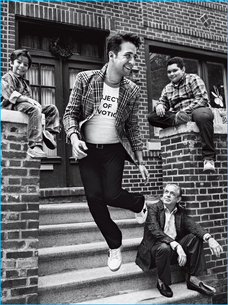 Captured in a black & white photo, Lin-Manuel Miranda wears a Prada sports jacket and pants from Prada with an Icons t-shirt, and Golden Goose Deluxe Brand sneakers for GQ.