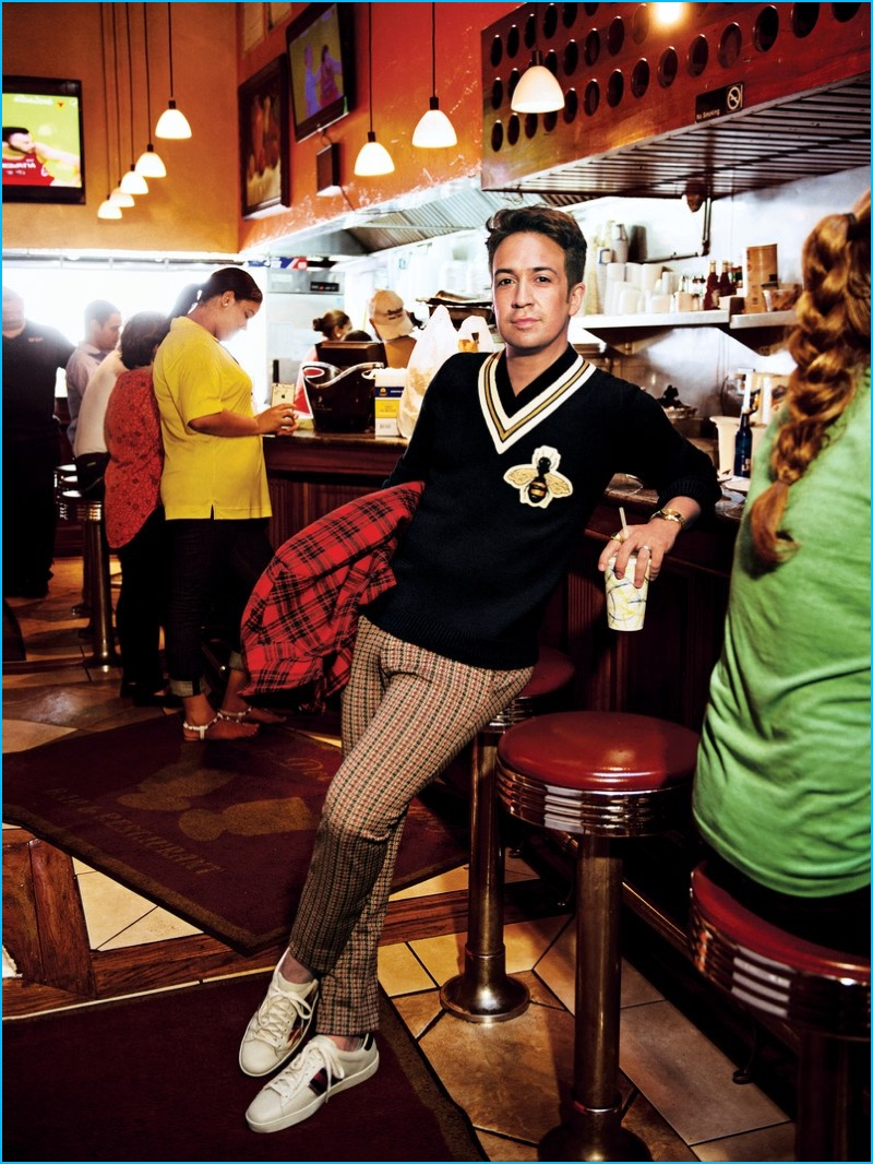 Lin-Manuel Miranda embraces preppy style in a varsity sweater, check trousers and sneakers from Gucci for GQ.