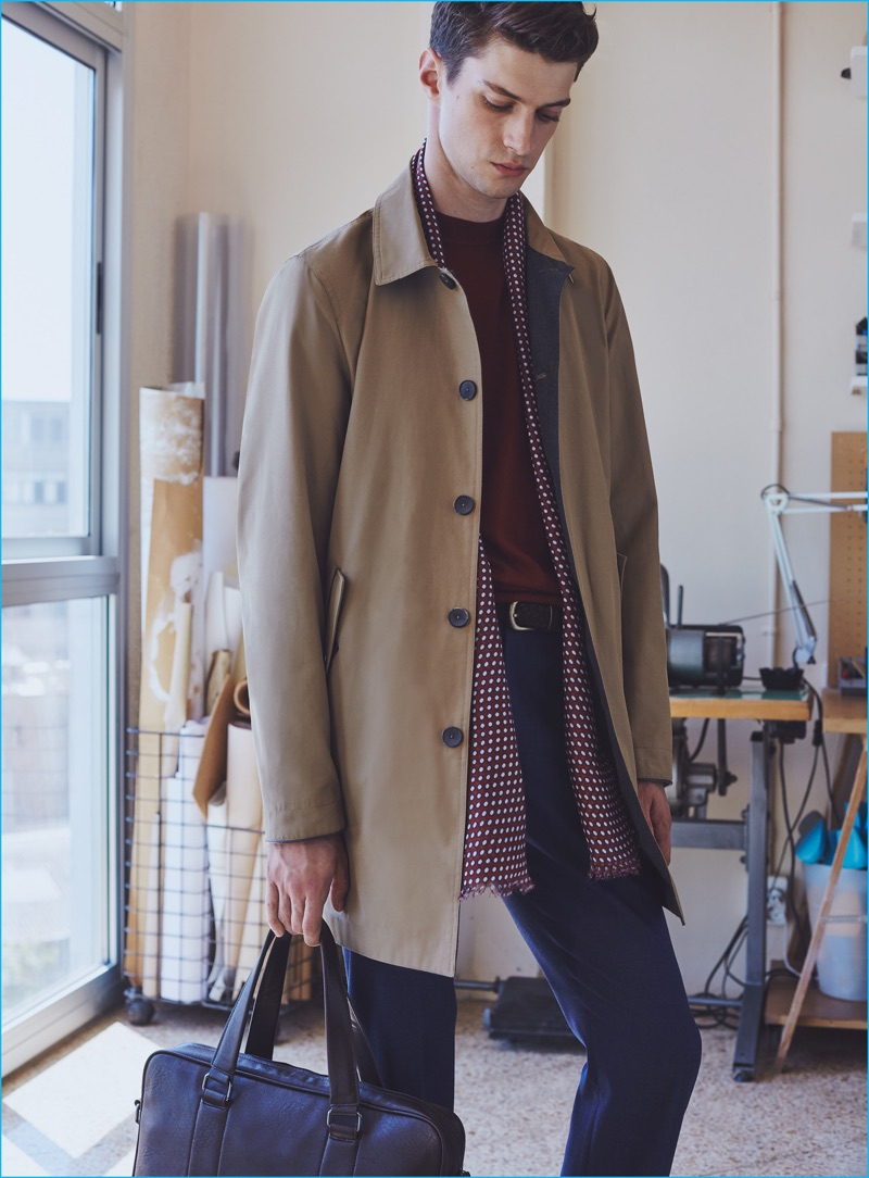 Matthew Bell pictured in a nylon trench coat, accessorized with a patterned scarf from Mango Man.