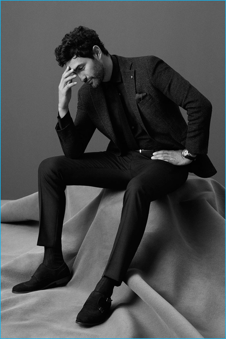 Noah Mills embraces slim lines in pleated trousers and a tweed sport coat from Massimo Dutti.