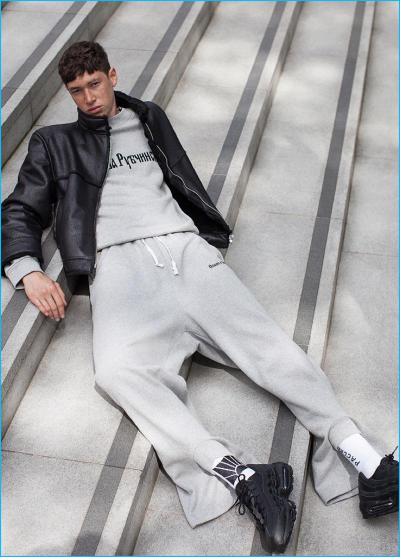Jos Whiteman wears leather jacket, sweatshirt, and sweatpants Gosha Rubchinskiy, and sneakers Nike.