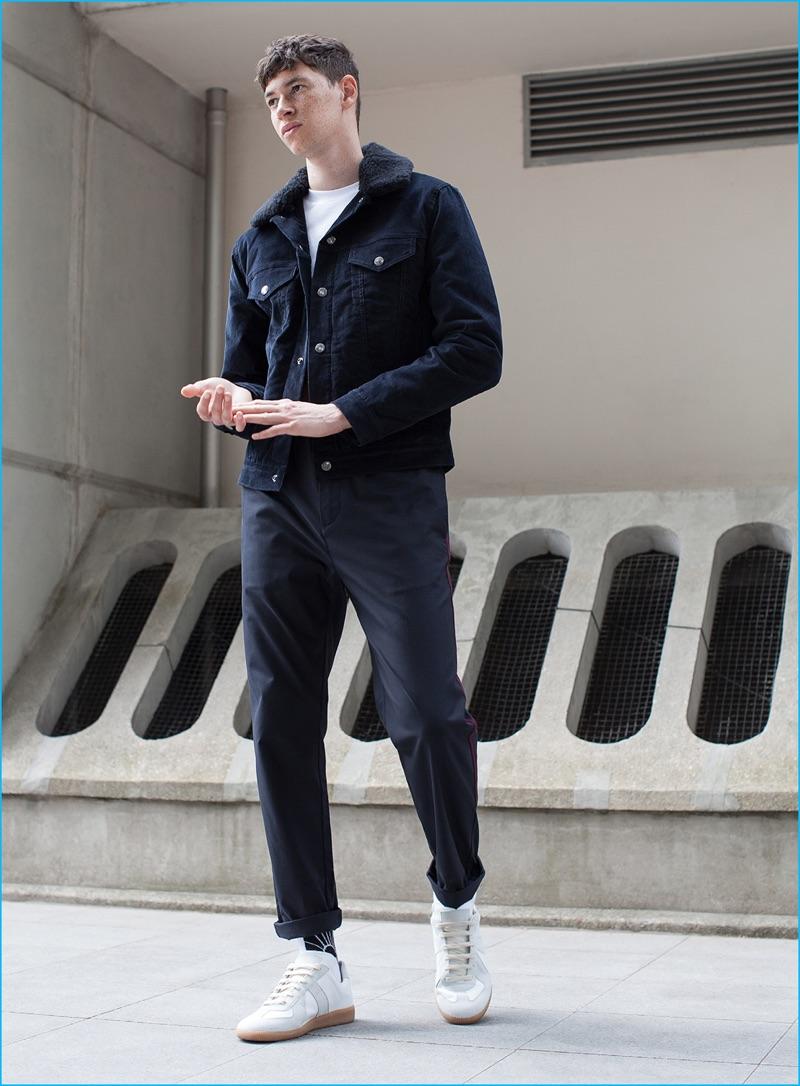 Jos Whiteman wears corduroy jacket Acne Studios, navy pants OAMC, and white sneakers Maison Margiela.