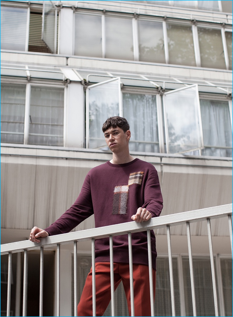 Jos Whiteman wears burgundy plaid sweatshirt and orange rust trousers CMMN SWDN.