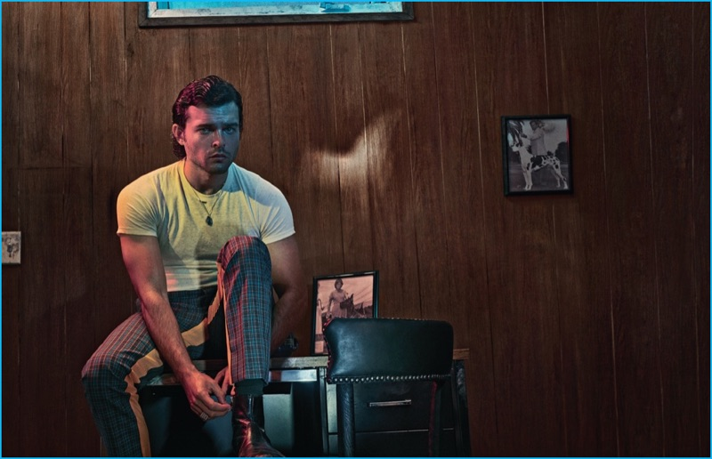 Beat Bolliger outfits Alden Ehrenreich in a vintage Munsingwear t-shirt with check Prada trousers for Interview magazine.