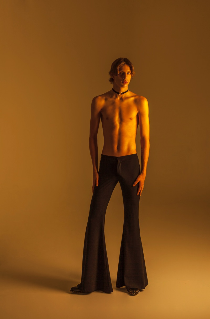 Chris wears choker Zara, flared trousers COS, and studded shoes Givenchy.