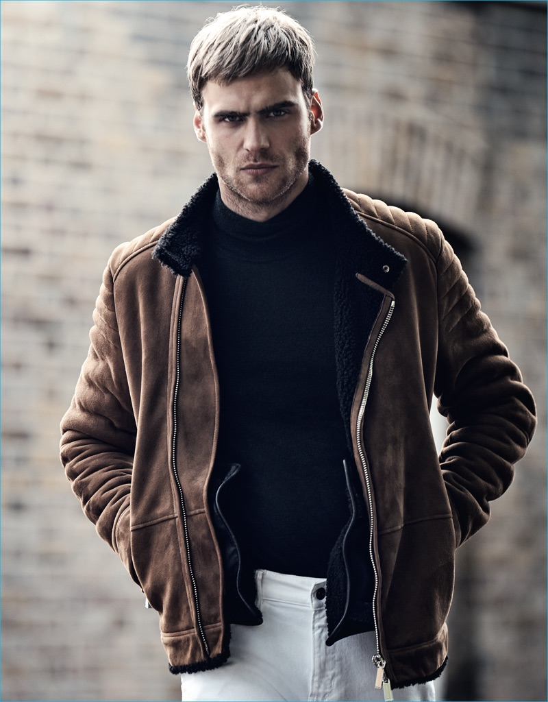 George Alsford dons a brown suede moto jacket with a mock turtleneck sweater, and white jeans from BOSS Hugo Boss for GQ France.