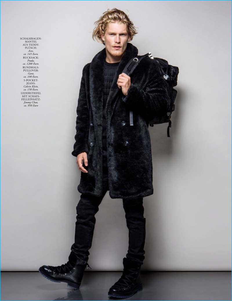 English model Harry Goodwins puts a foot forward, wearing Jimmy Choo boots, an ASOS coat, Prada backpack, Gant sweaer, and Calvin Klein jeans.