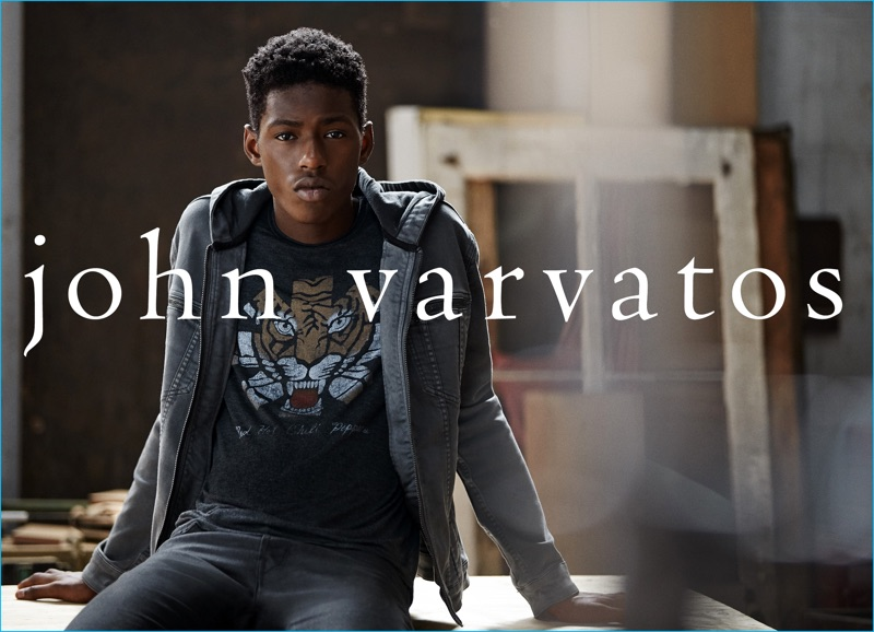 Sheani Gist goes casual in a graphic t-shirt, hoodie, and jeans from John Varvatos.