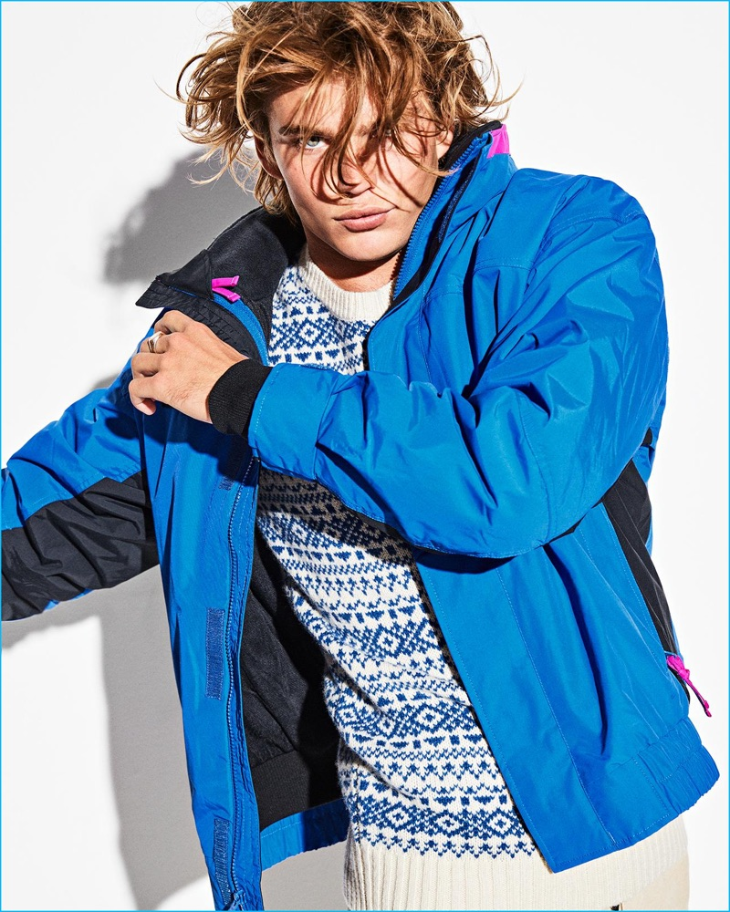 Tackling casual styles, Jordan Barrett wears a Penfield sweater with a blue Columbia jacket.
