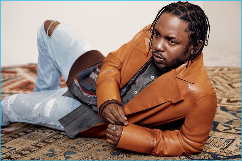 Appearing in a photo shoot for GQ Style's holiday issue, Kendrick Lamar wears a brown leather coat from Berluti. Lamar also wears a Berluti cardigan and Ami shirt.