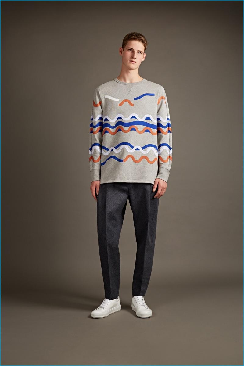 Acne Studios fun print sweatshirt, pleated trousers, and white sneakers.
