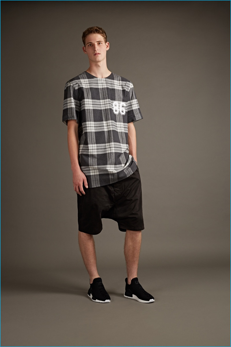 Helmut Lang oversized plaid t-shirt and black side stripe neoprene shorts with Y-3 high sneakers.