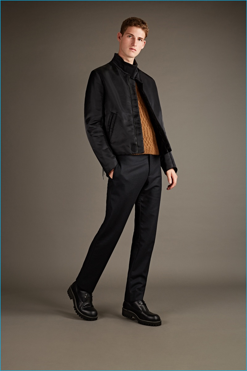 Maison Margiela black denim jacket, cable-knit sweater, chinos, and chunky soled shoes.