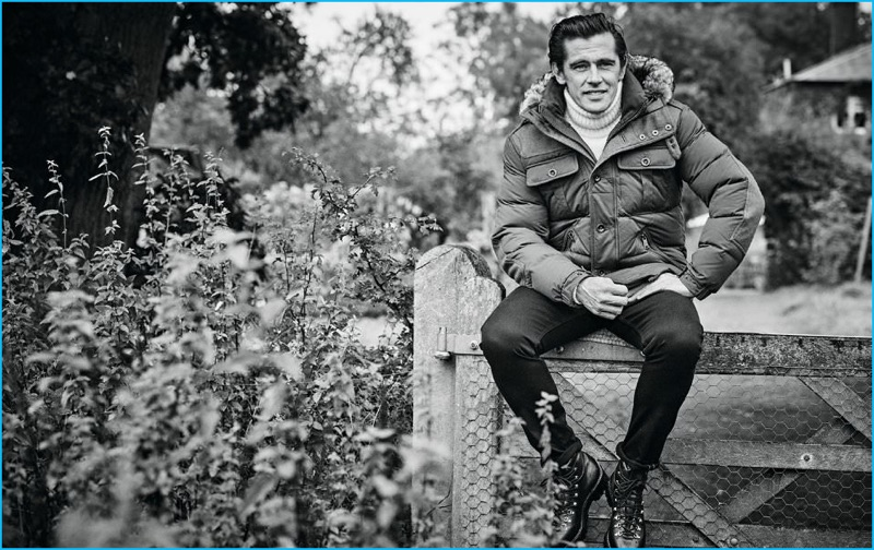 Sitting for a black & white picture, Werner Schreyer wears a faux fur-trimmed hooded parka, cashmere turtleneck sweater, slim-fit denim jeans, and leather boots from Ralph Lauren Purple Label.