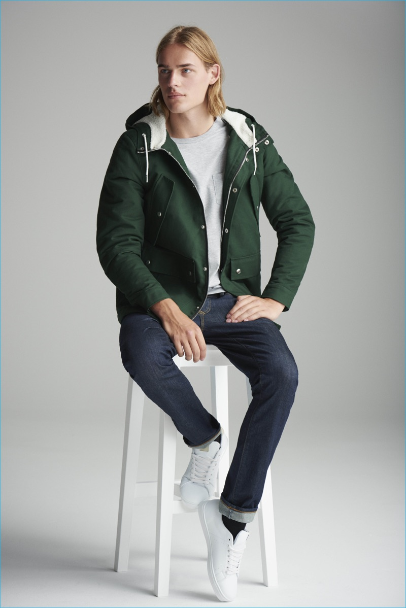 Ton Heukels goes sporty in a green hooded jacket and jeans for River Island's fall-winter 2016 denim campaign.