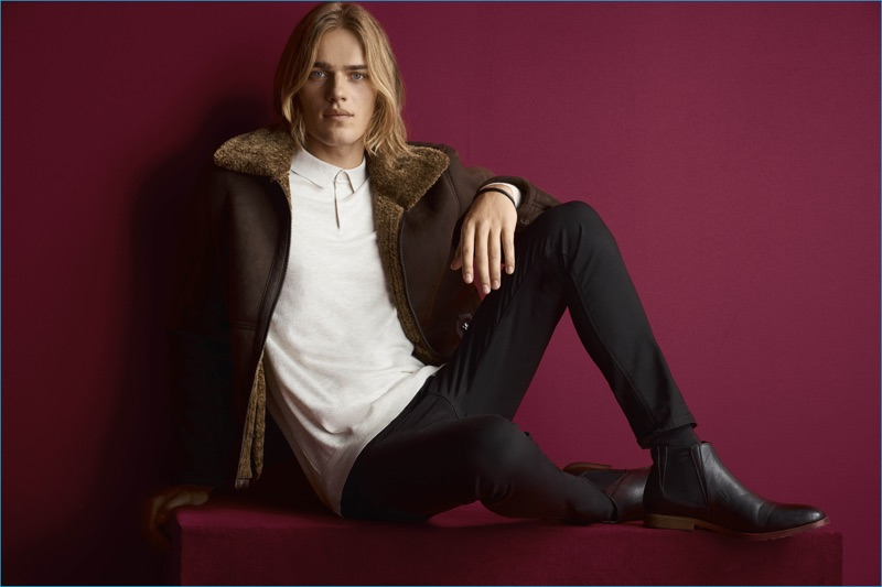 Sporting fall style, Ton Heukels models a shearling jacket with black jeans and a polo shirt from River Island.